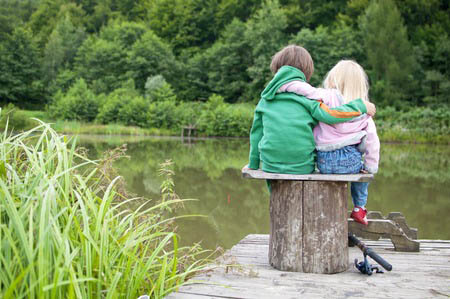 31713570 - two little child hug each other and look a the lake view